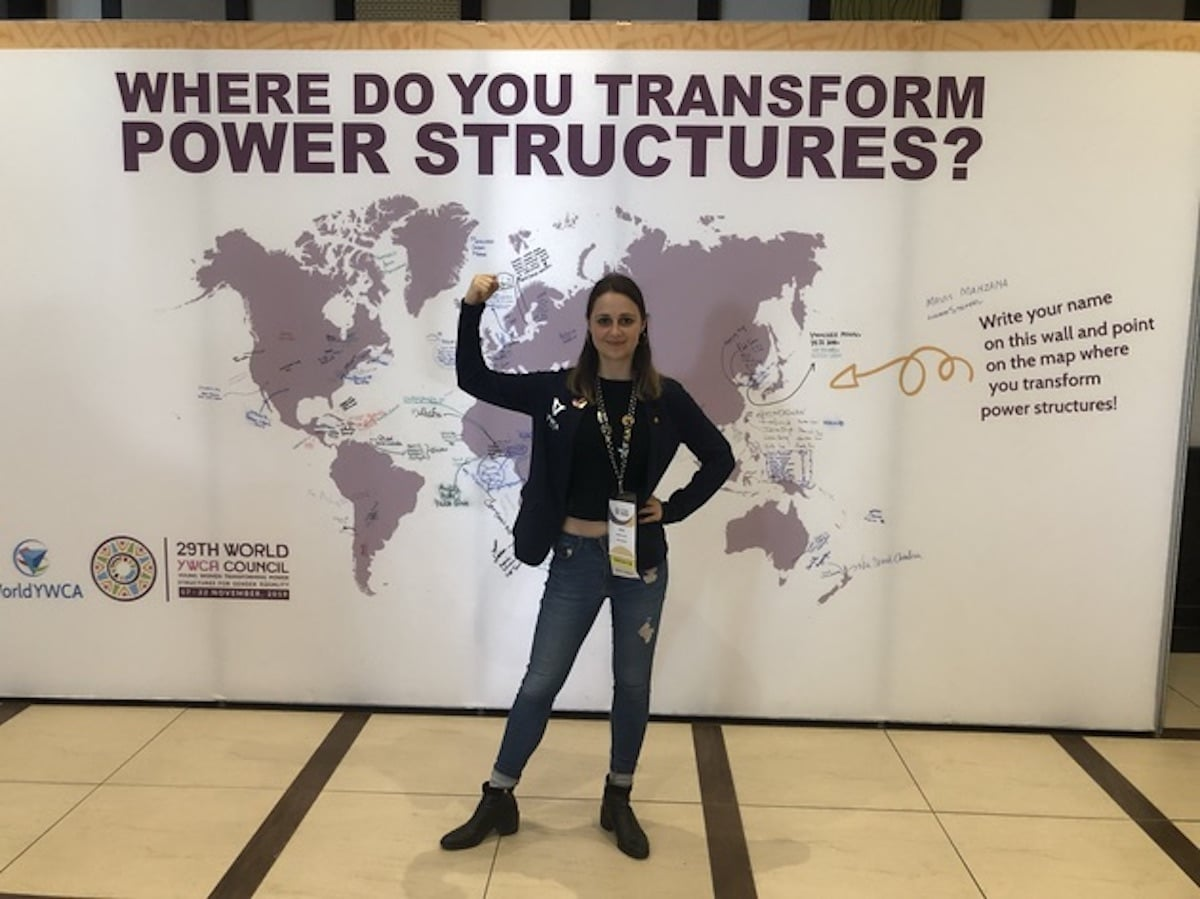 Image of Ashleigh Streeter in front of a poster at the world YWCA conference