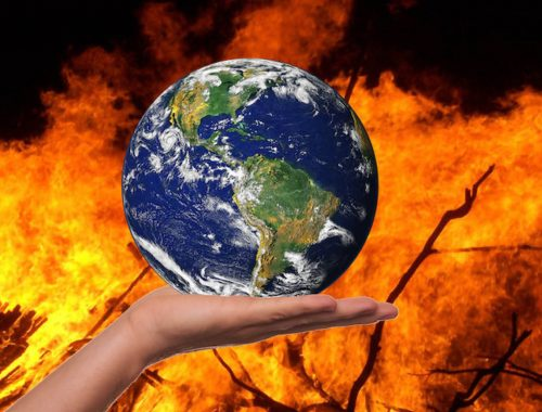 Earth in the palm of someone's hand with fire int he background