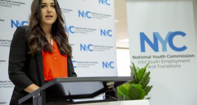 IMage of Sophie Johnston standing at a podium speaking, with a screen in the background saying NYC
