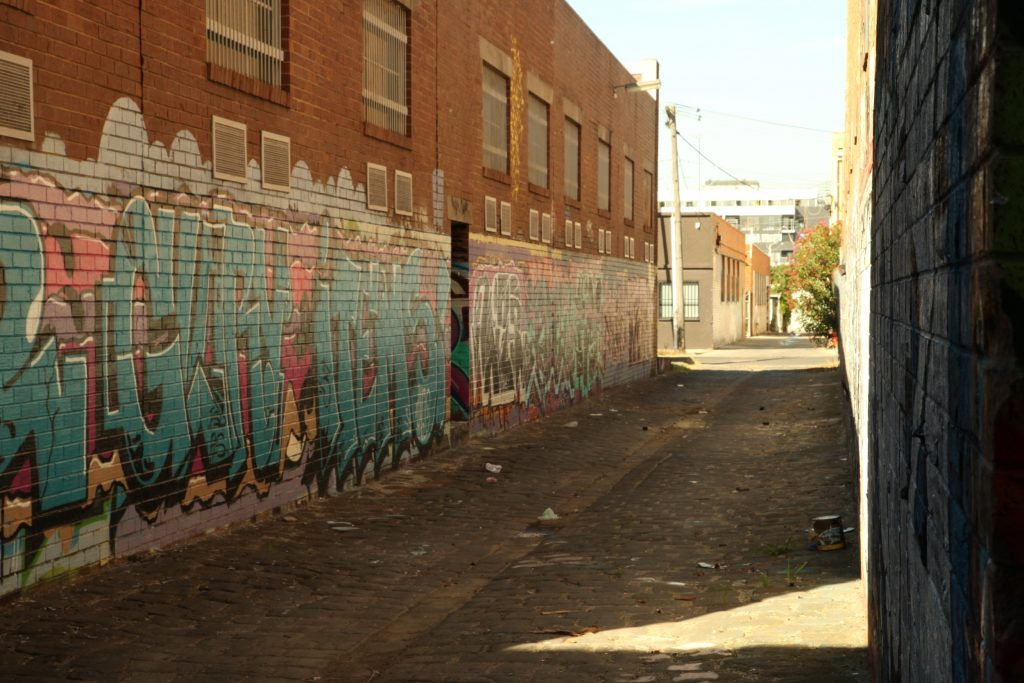 Image of an empty alleyway with graffiti on the walls
