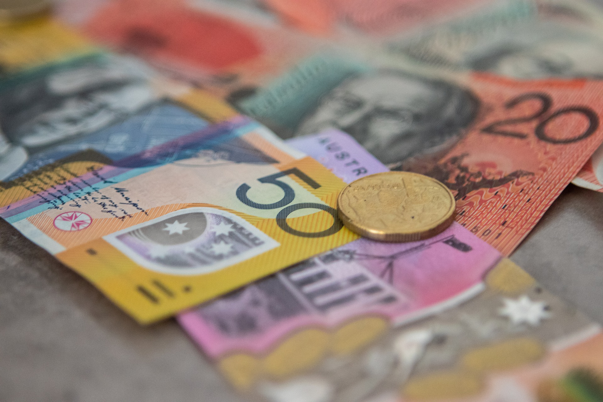 Image of Australian currency one dollar coin, 50 dollar note, 5 dollar note and 20 dollar note.