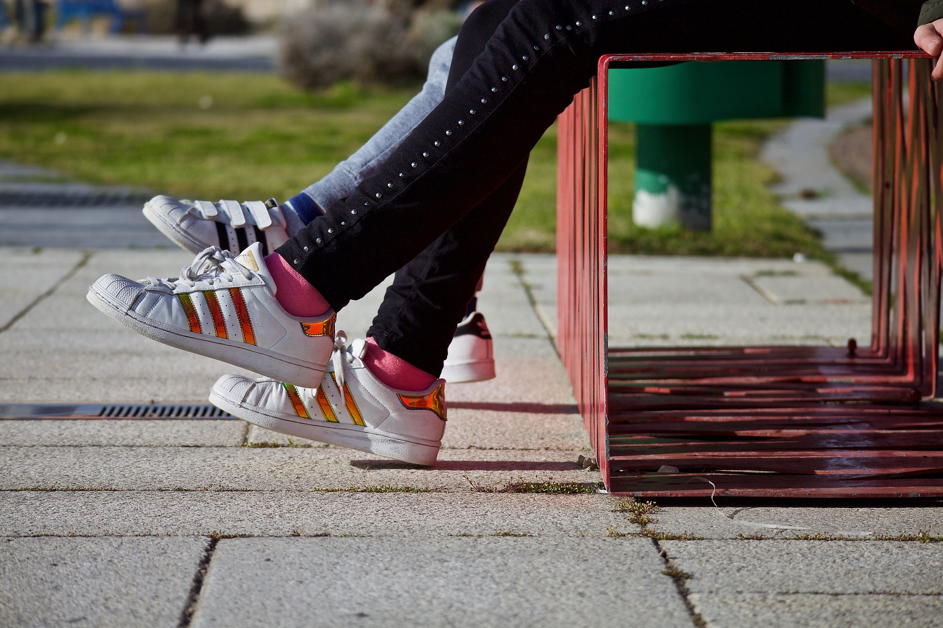 Image of two people sitting on a bench from the waist down with jeans and sneakers on